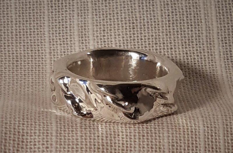 Silverring med 'flätor' längs hela utsidan